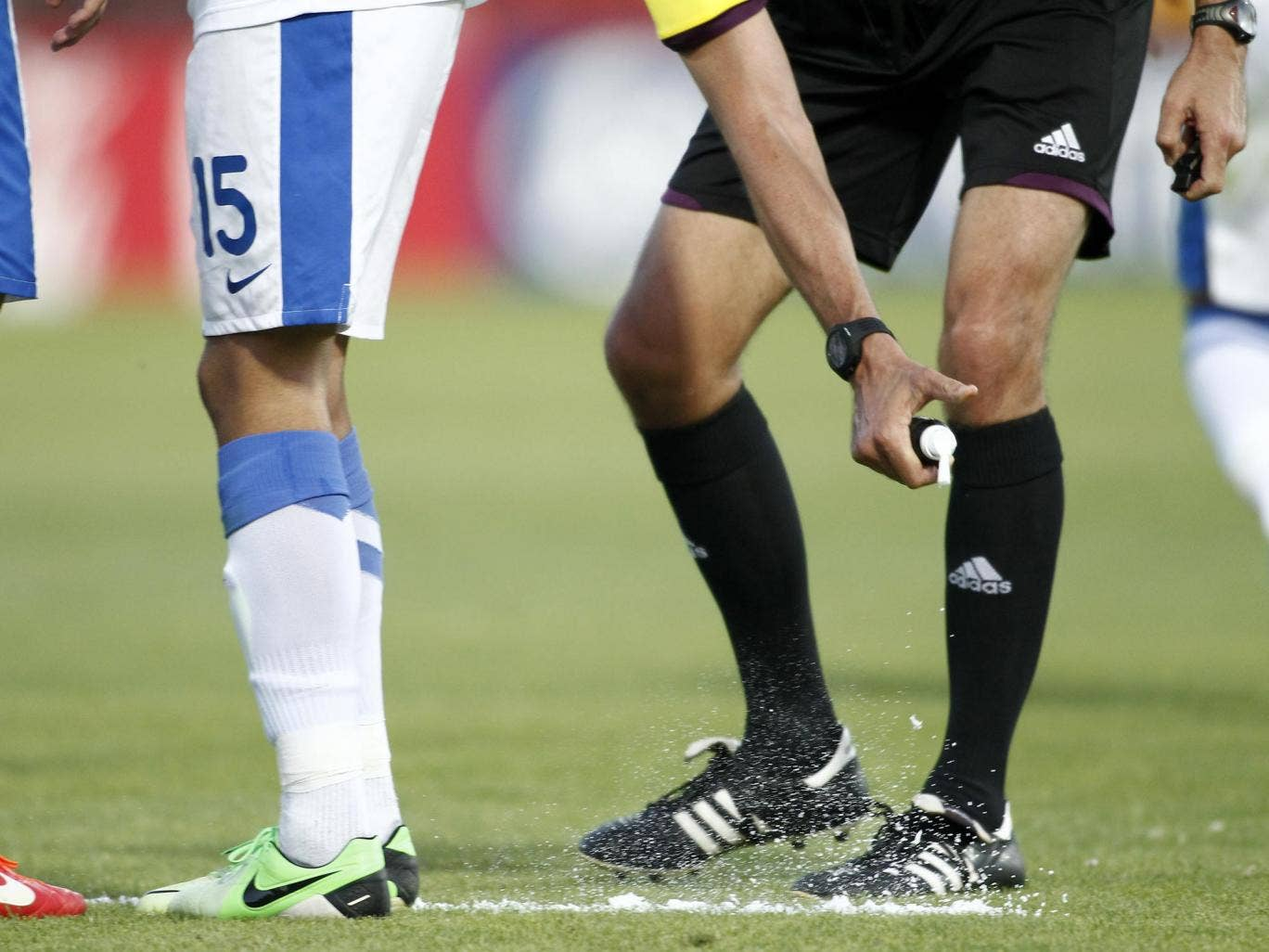 A referee uses vanishing spray