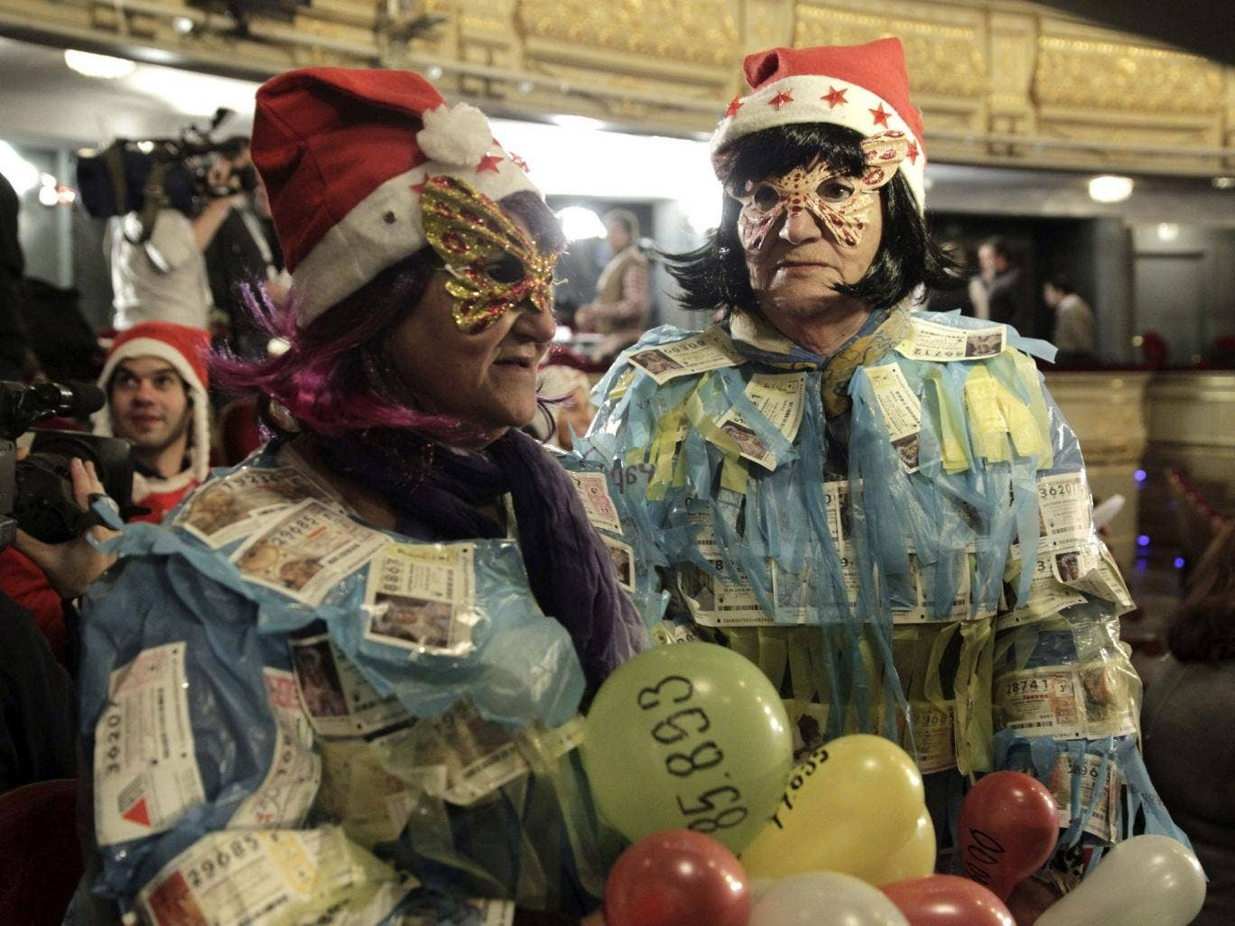 Two women display 'El Gordo' lottery tickets on their bodies as they wait for the beginning of the draw at Madrid's Teatro Real