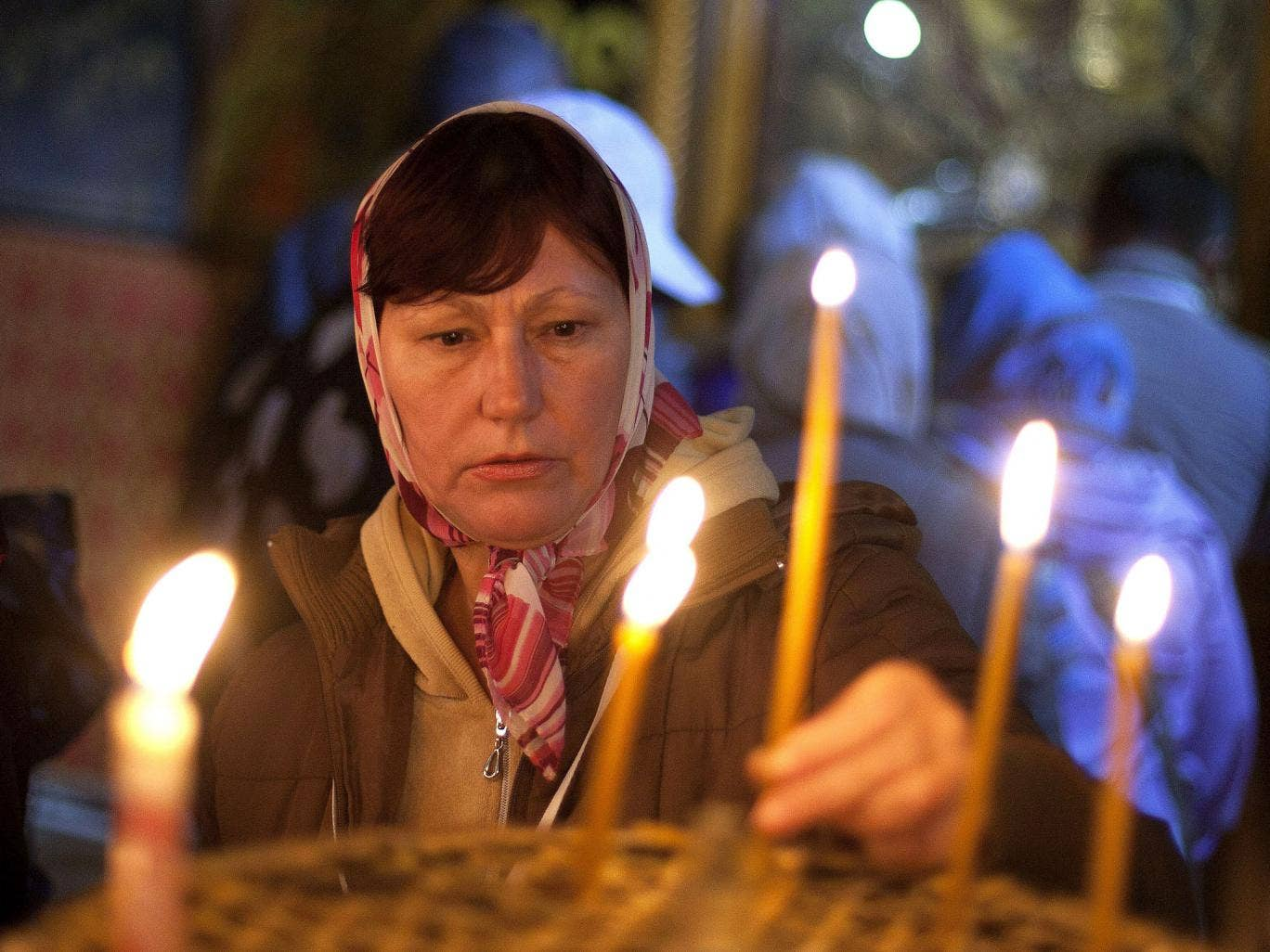 A worshipper lights candles at the Church of the Nativity