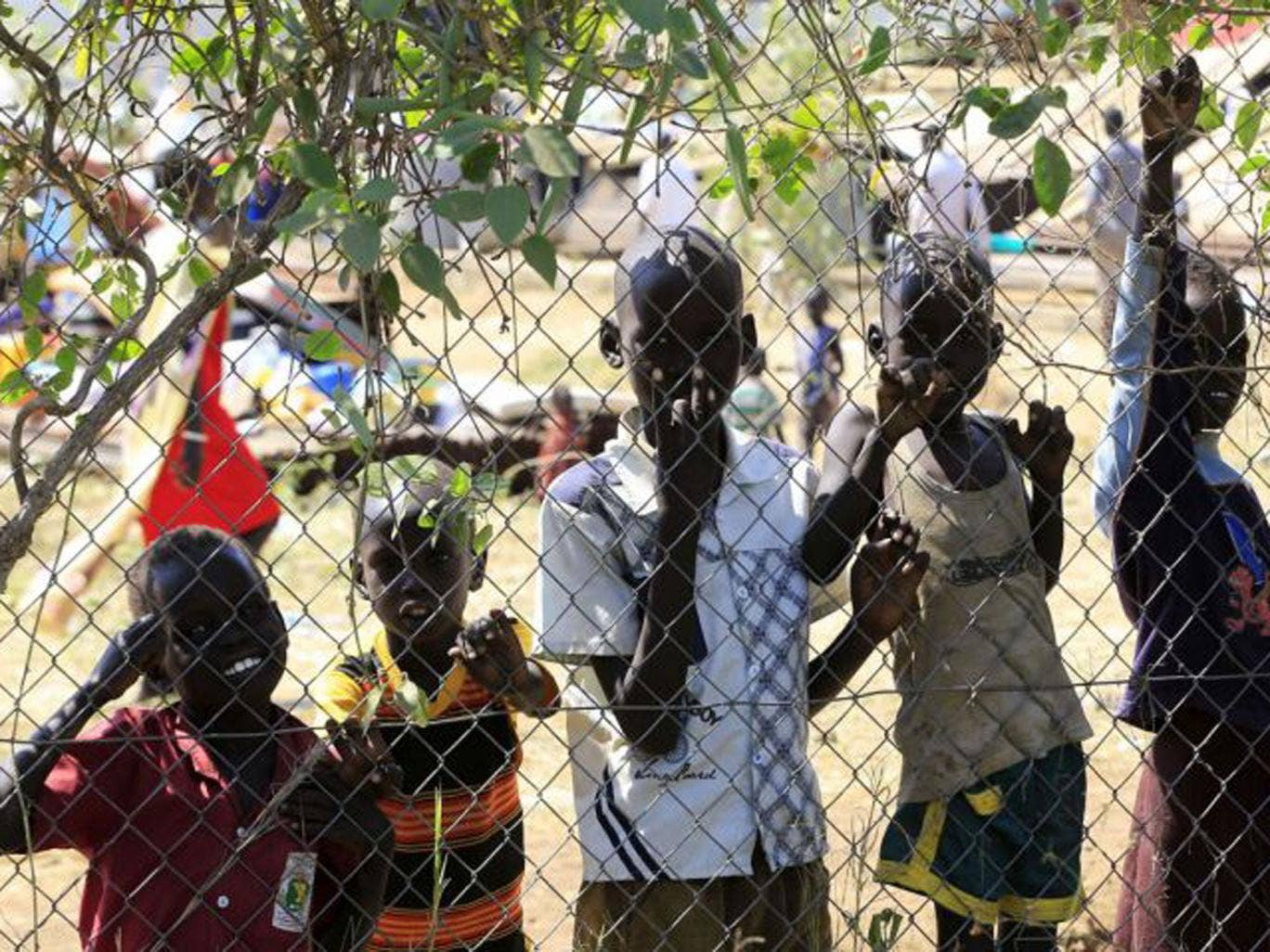 Children displaced by the fighting in South Sudan wait behind the fence of the United Nations Mission facility on the outskirts of the capital Juba. Tens of thousands of refugees have fled the crisis