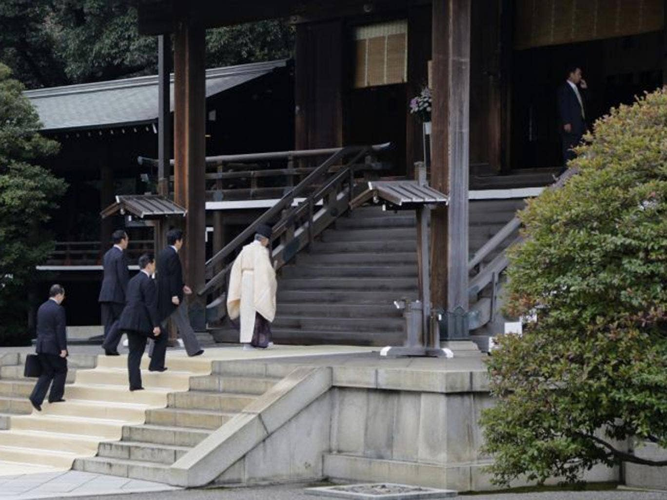 Japan's Prime Minister Shinzo Abe is led by a Shinto priest as he visits Yasukuni shrine in Tokyo