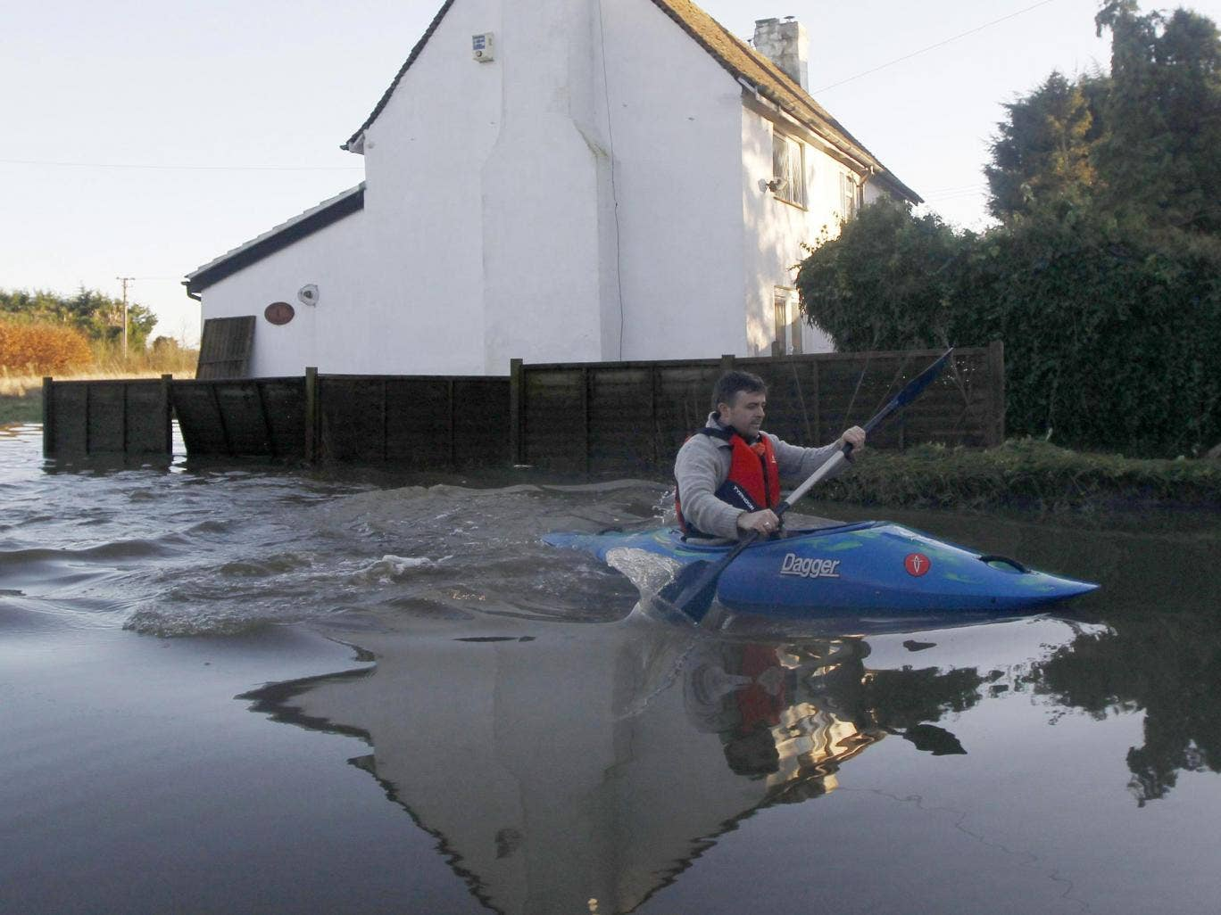 A man paddles through the flood waters in Yalding
