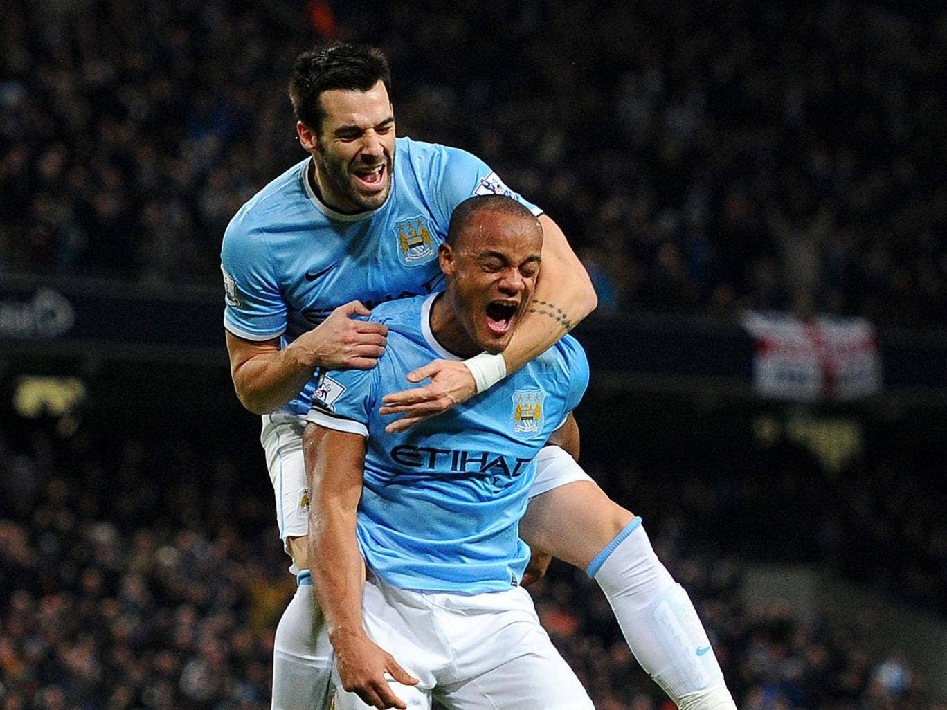 Manchester City's match-winner Alvaro Negredo (top) celebrates with his fellow goalscorer Vincent Kompany at the Etihad