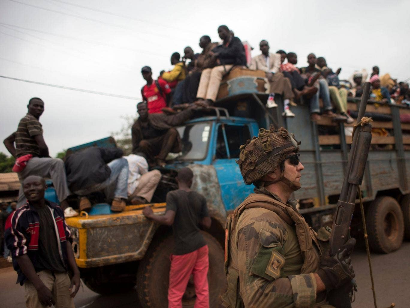 French soldiers protect a truck of fleeing Muslims after it broke down and was surrounded by hundreds of hostile Christian residents in the Gobongo neighborhood of Bangui - Red Cross workers said they had recovered 44 bodies from the streets of the capita