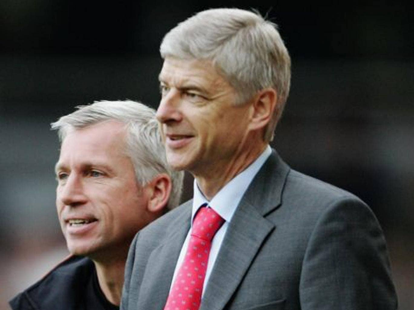 Beside themselves: Alan Pardew (left) does not see eye to eye with Arsène Wenger but says 'we owe him a bit of a debt'