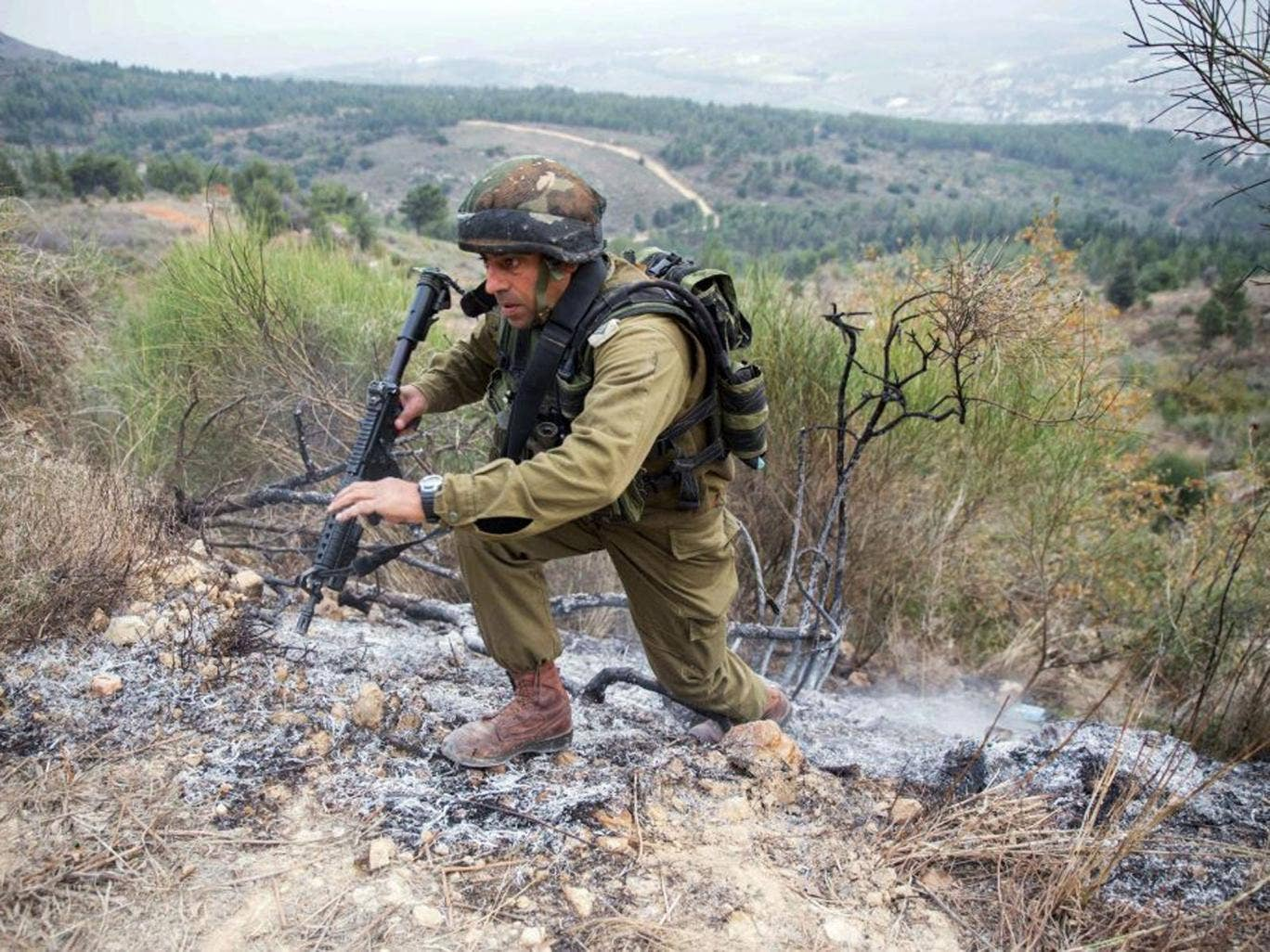 An Israeli army officer inspects the area where a Katyusha rocket fired from militants inside southern Lebanon landed along Israel's northern border to the west of Kiryat Shemona