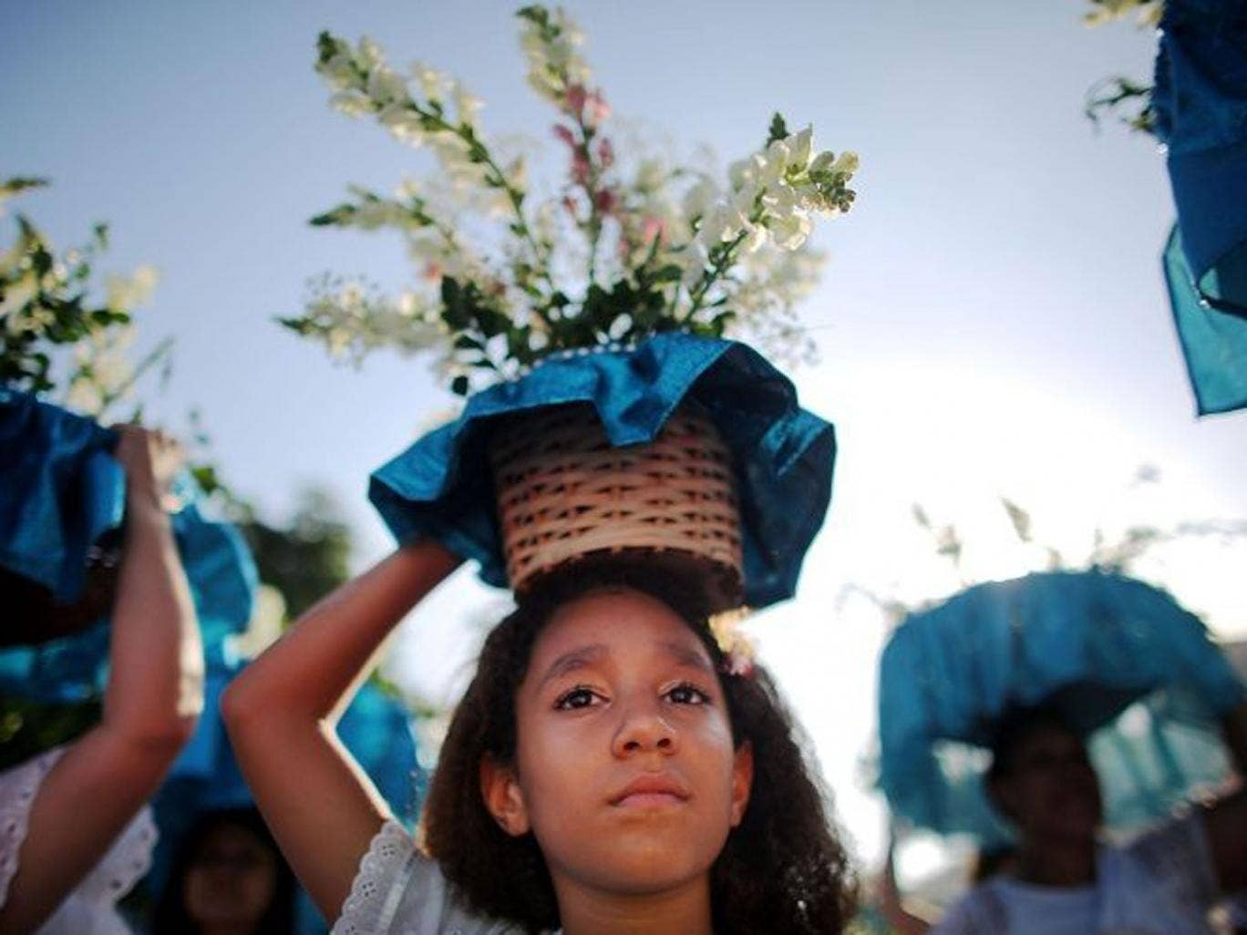 Women carry offerings at a ceremony honoring Iemanja, Goddess of the Sea, as part of traditional New Year's celebrations on the sands of Copacabana beach in Rio de Janeiro