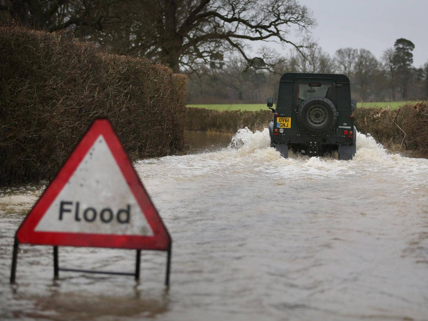 A Landrover makes it's way along a flooded road near Lingfield