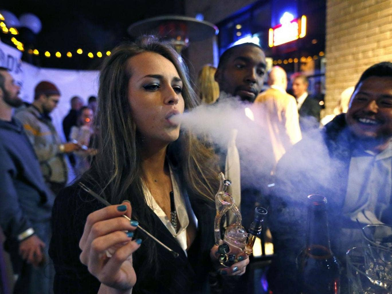Partygoers smoke marijuana during a Prohibition-era themed New Year's Eve party celebrating the start of retail pot sales in Denver