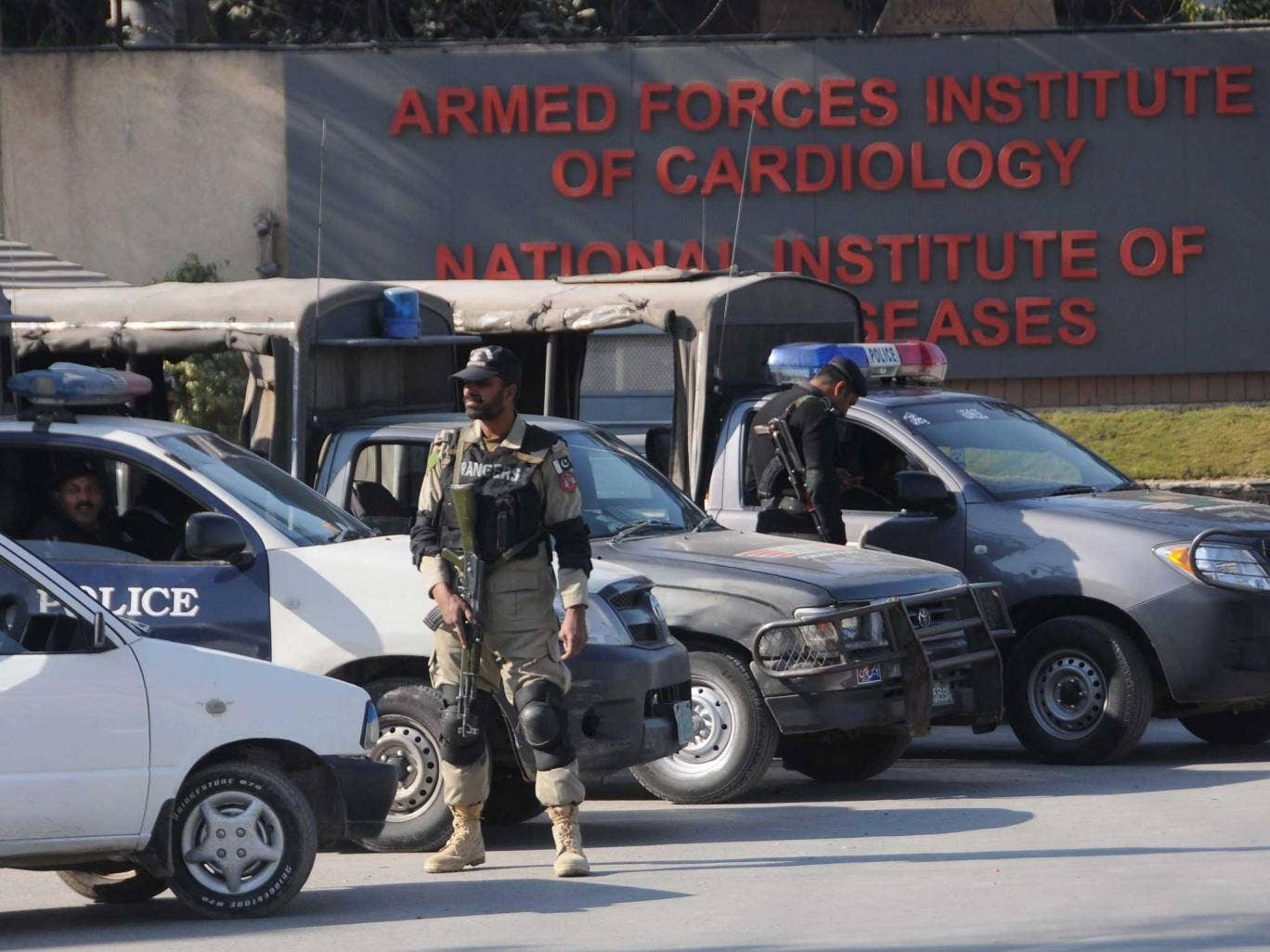 Pakistani security officials stand guard outside the Armed Forces Institute of Cardiology hospital where former President Pervez Musharraf is receiving medical treatment