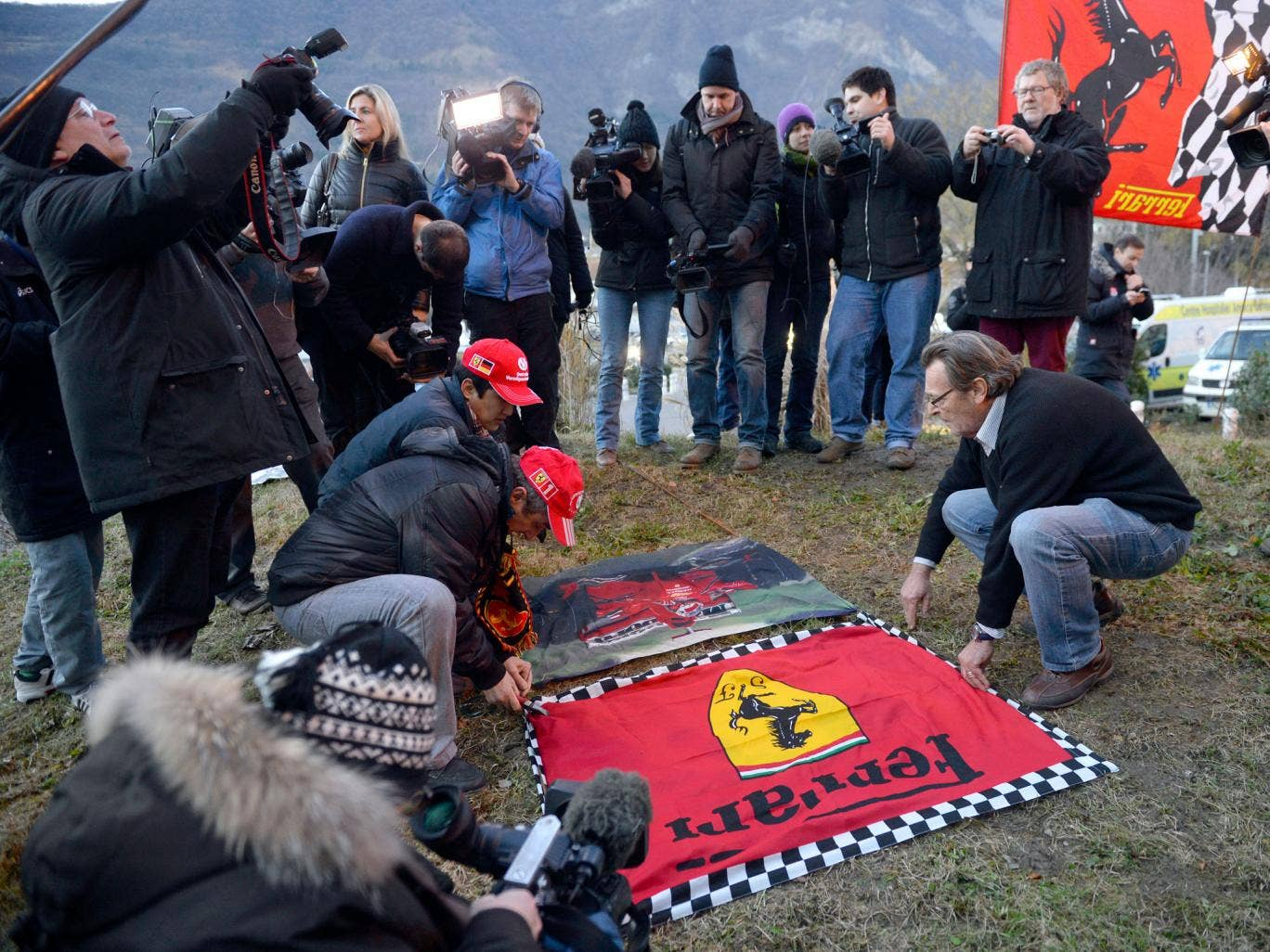 Fans of Michael Schumacher and Ferrari lay down flags to support the former F1 world champion in a show of support as he continues to fight for his life