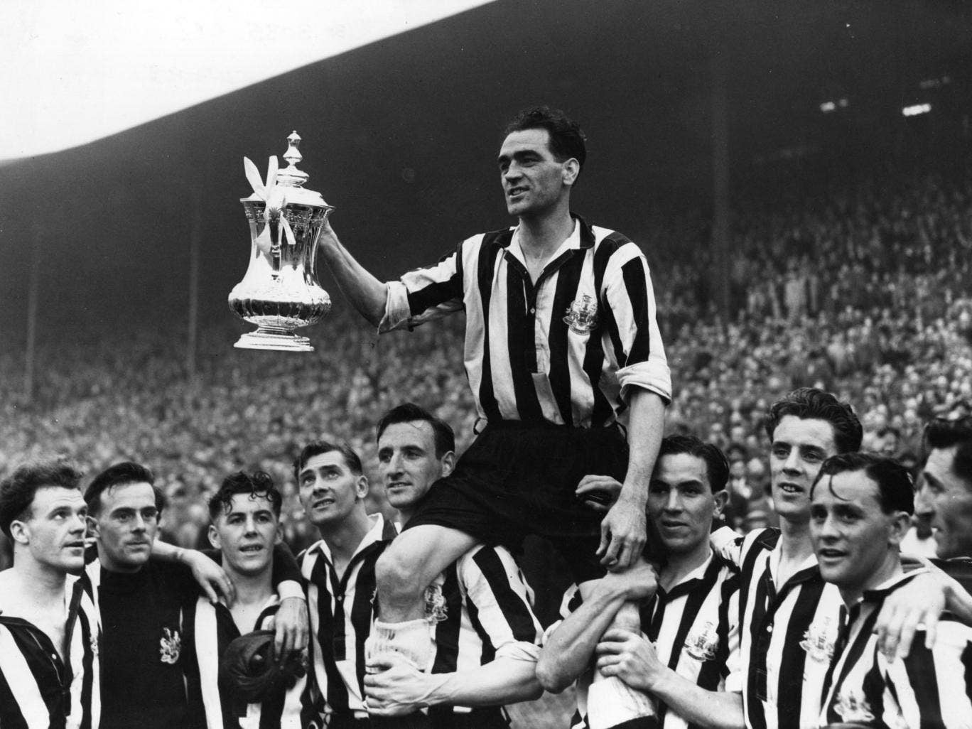 Newcastle United's captain Joe Harvey raises the FA Cup at Wembley in 1952