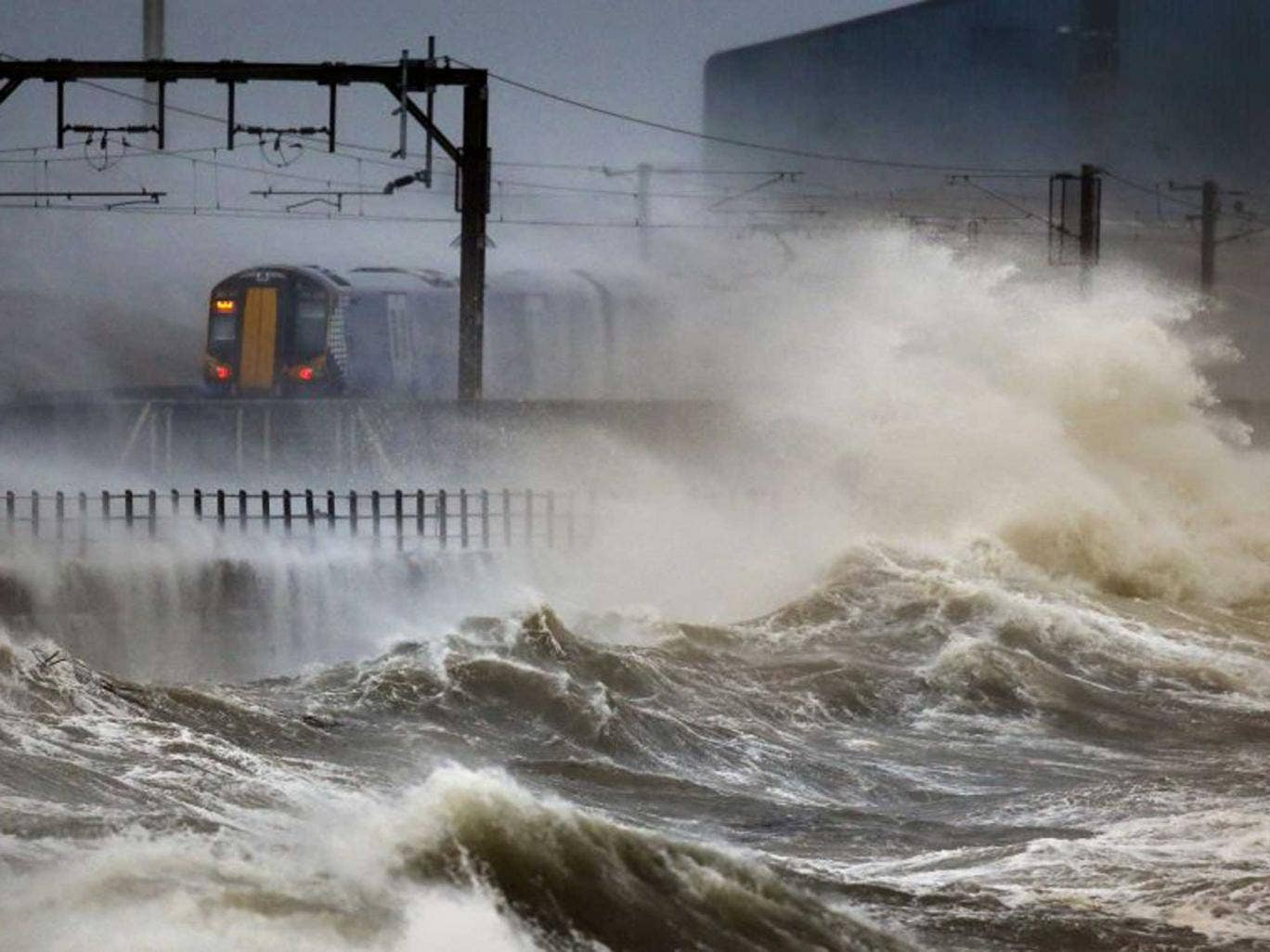 A train passes along the coast at Saltcoats in Scotland, as a combination of high tides, heavy rains and strong winds are expected to bring yet more severe flooding to many parts of the country