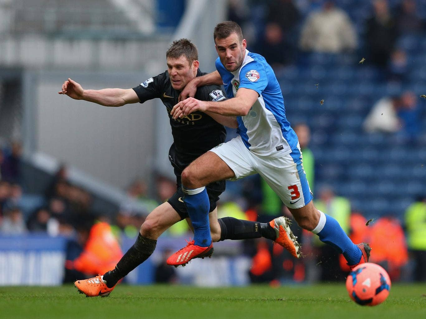 Tommy Spurr of Blackburn Rovers competes with James Milner of Manchester City