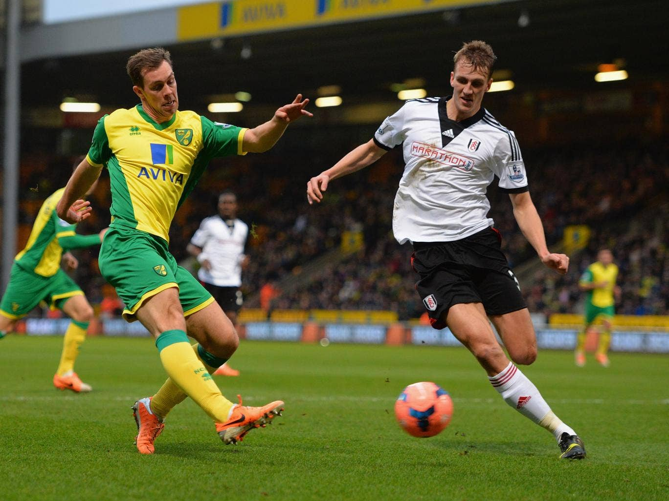 Norwich right-back Steven Whittaker tries to shoot past Fulham defender Dan Burn