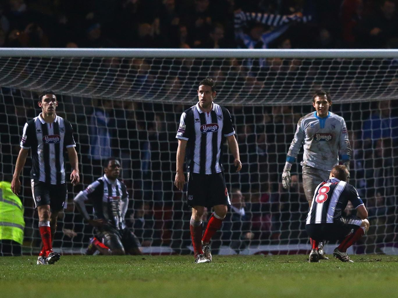 Grimsby players look dejected after conceding a late goal to Huddersfield that saw them knocked out of the FA Cup
