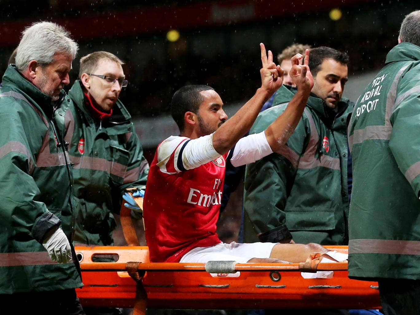 Theo Walcott gestures the scoreline to angry Spurs fans, who threw coins and plastic bottles in the direction of the Arsenal forward