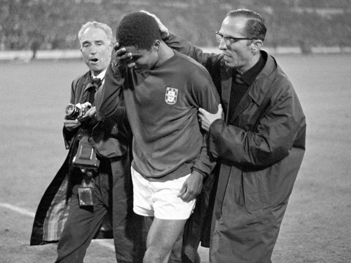 Portugal's Eusebio being consoled by a compatriot as he leaves the field in tears after Portugal had been defeated 1-2 by England in the 1966 World Cup semi-final at Wembley