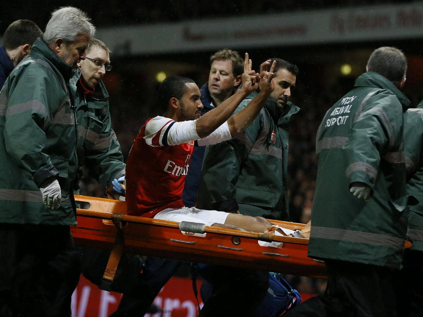 Arsenal's Theo Walcott makes the '2-0' gesture to Spurs fans as he is carried off