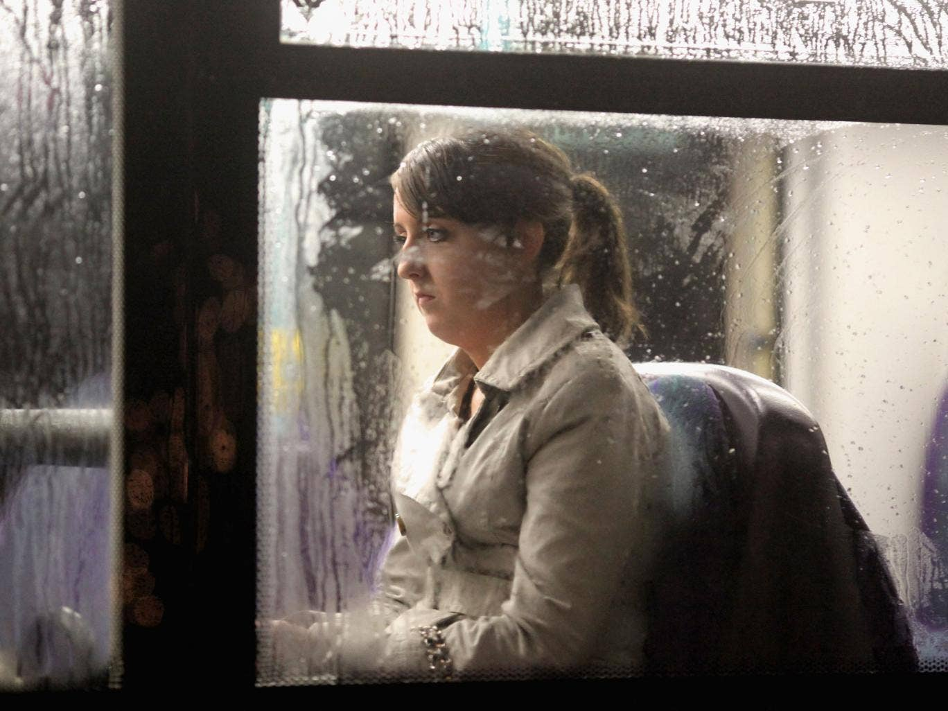 A woman sits on a bus as it makes its way along St Vincent Street