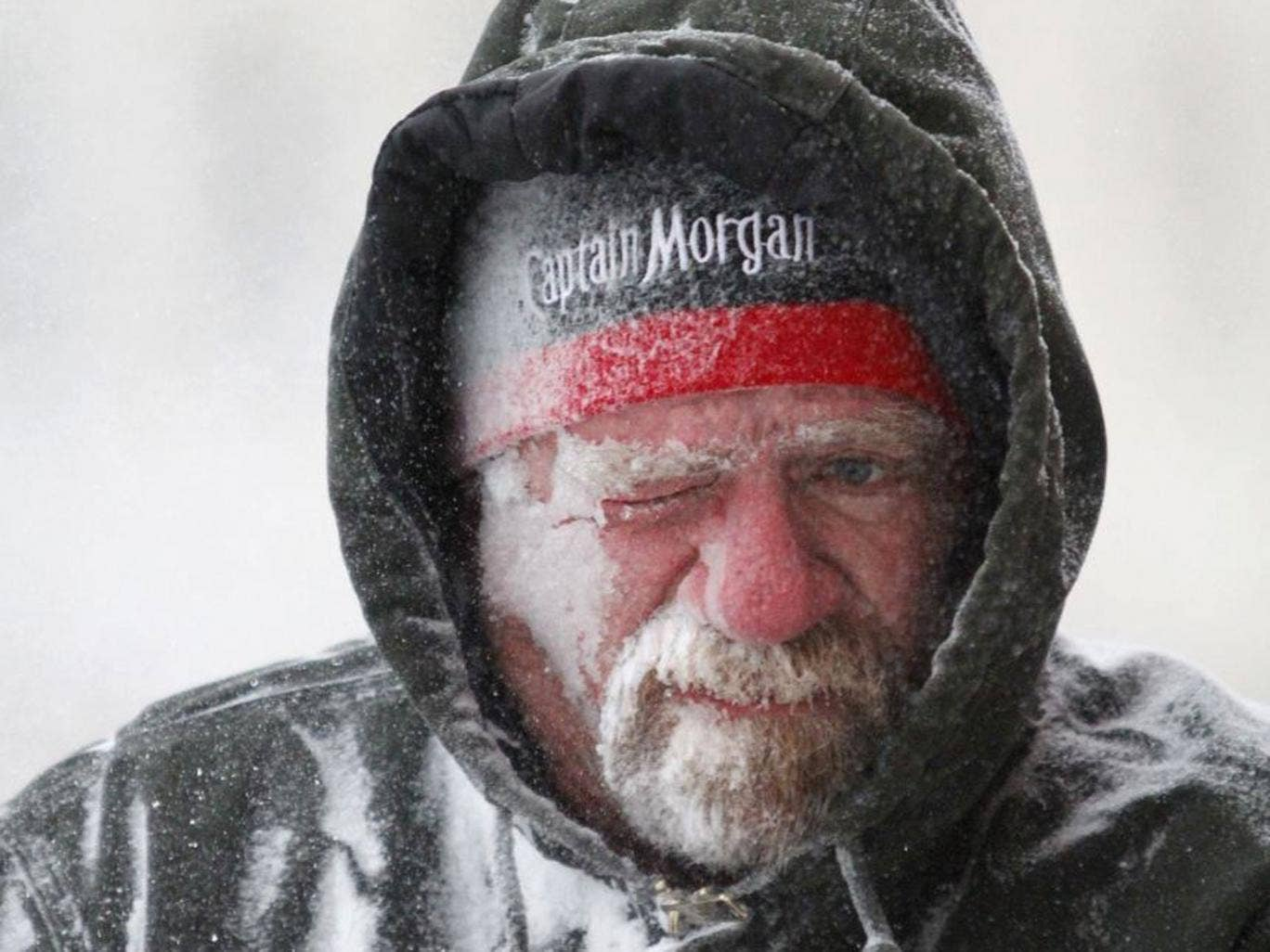 Allan Umscheid, owner of Yards By Al in Lawrence, Kan, feels the bitter wind and catches drifting snow on his face as he runs a snow blower early morning