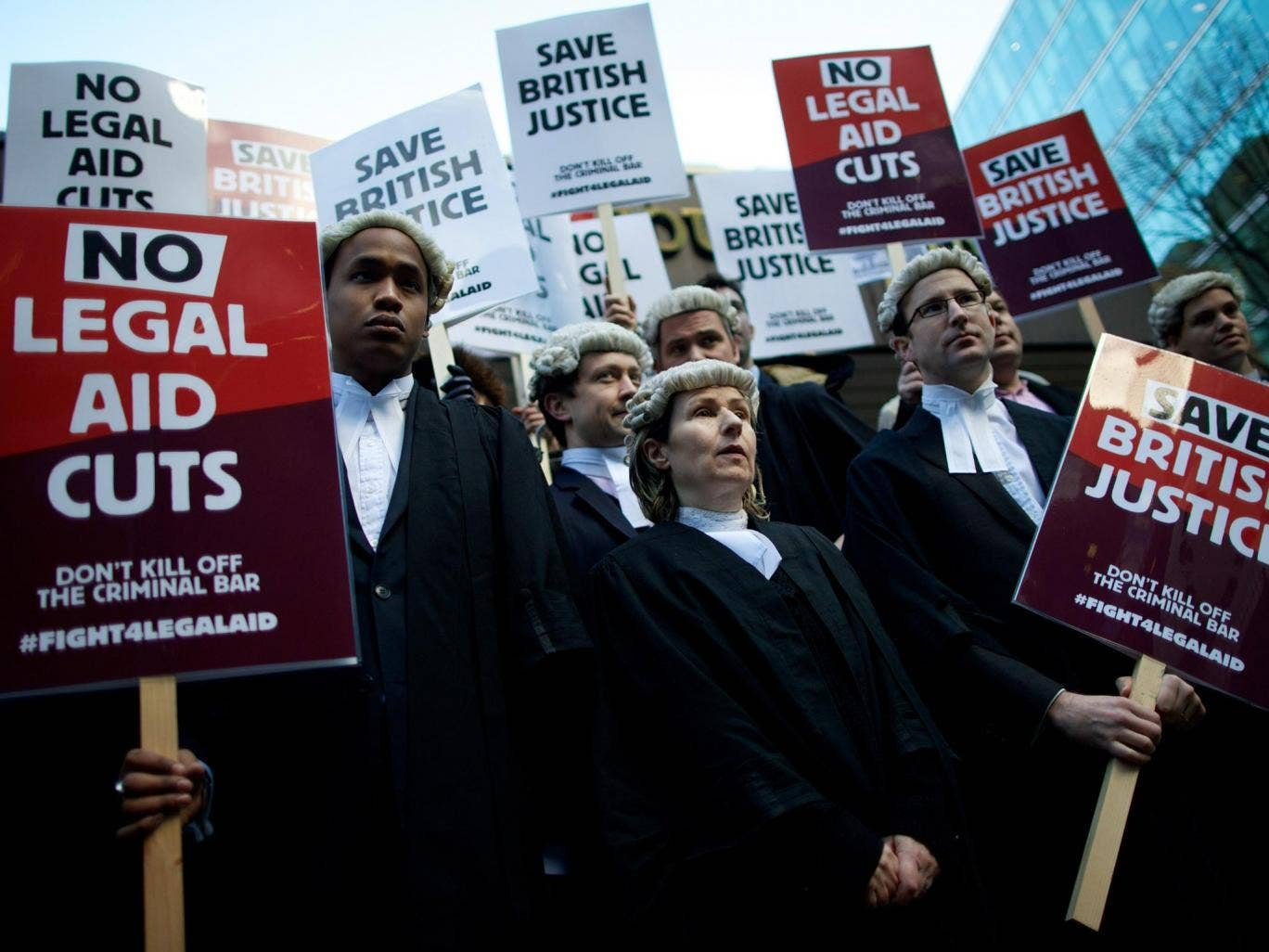 British legal professionals hold placards during a protest against cuts to the legal aid budget during a protest outside Southwark Crown Court