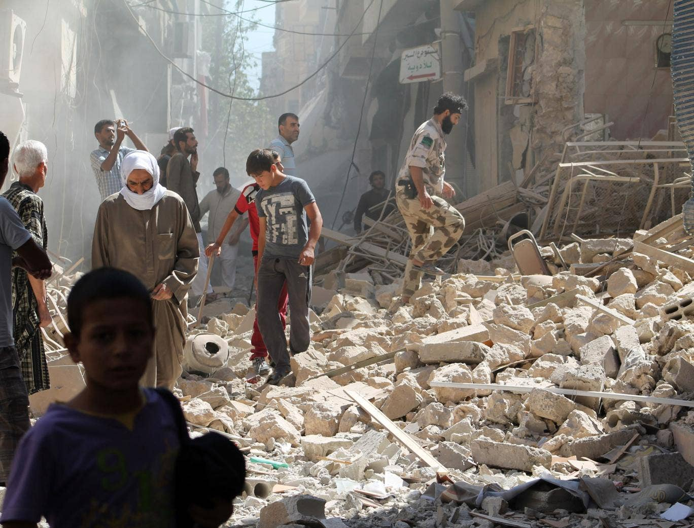 Residents of Syria's eastern town of Deir Ezzor walk past the debris of a building reportedly hit by a missile on September 26, 2013. The Syrian Observatory for Human Rights said that there was fighting between rebels and units of the jihadist Islamic Sta