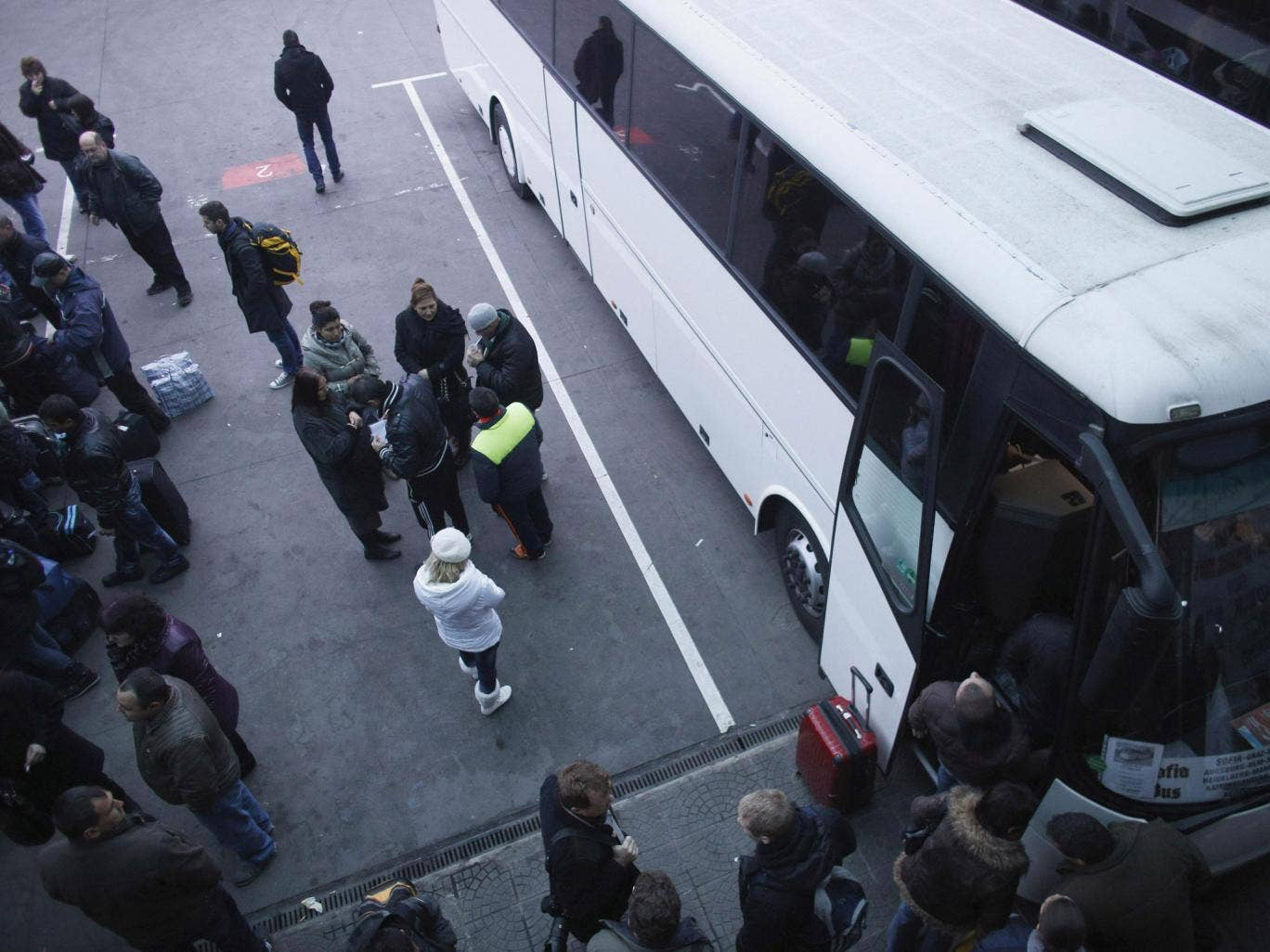 People stand next to a bus departing from Sofia's central bus station headed to London. Hostility to the current scale of immigration is increasing among the British public