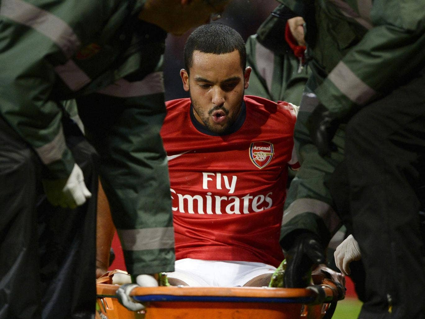 Theo Walcott is stretchered off the pitch during the match against Tottenham Hotspur