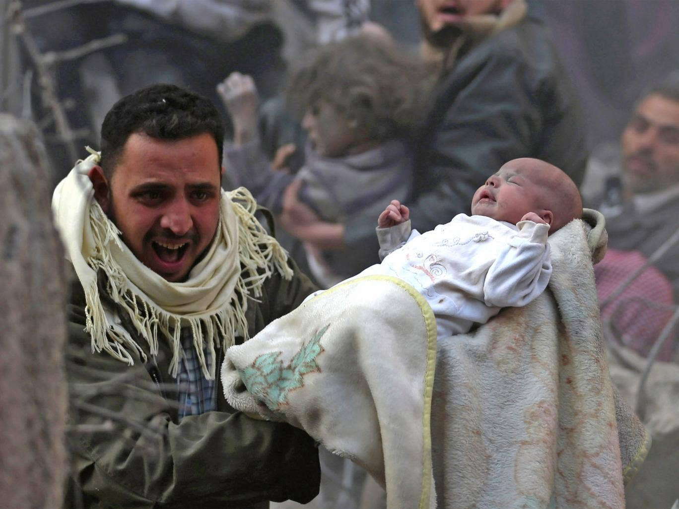 A man holds up a dust-covered baby who survived what activists say was an airstrike by forces loyal to the Syrian President, Bashar al-Assad, in the Duma neighbourhood of Damascus