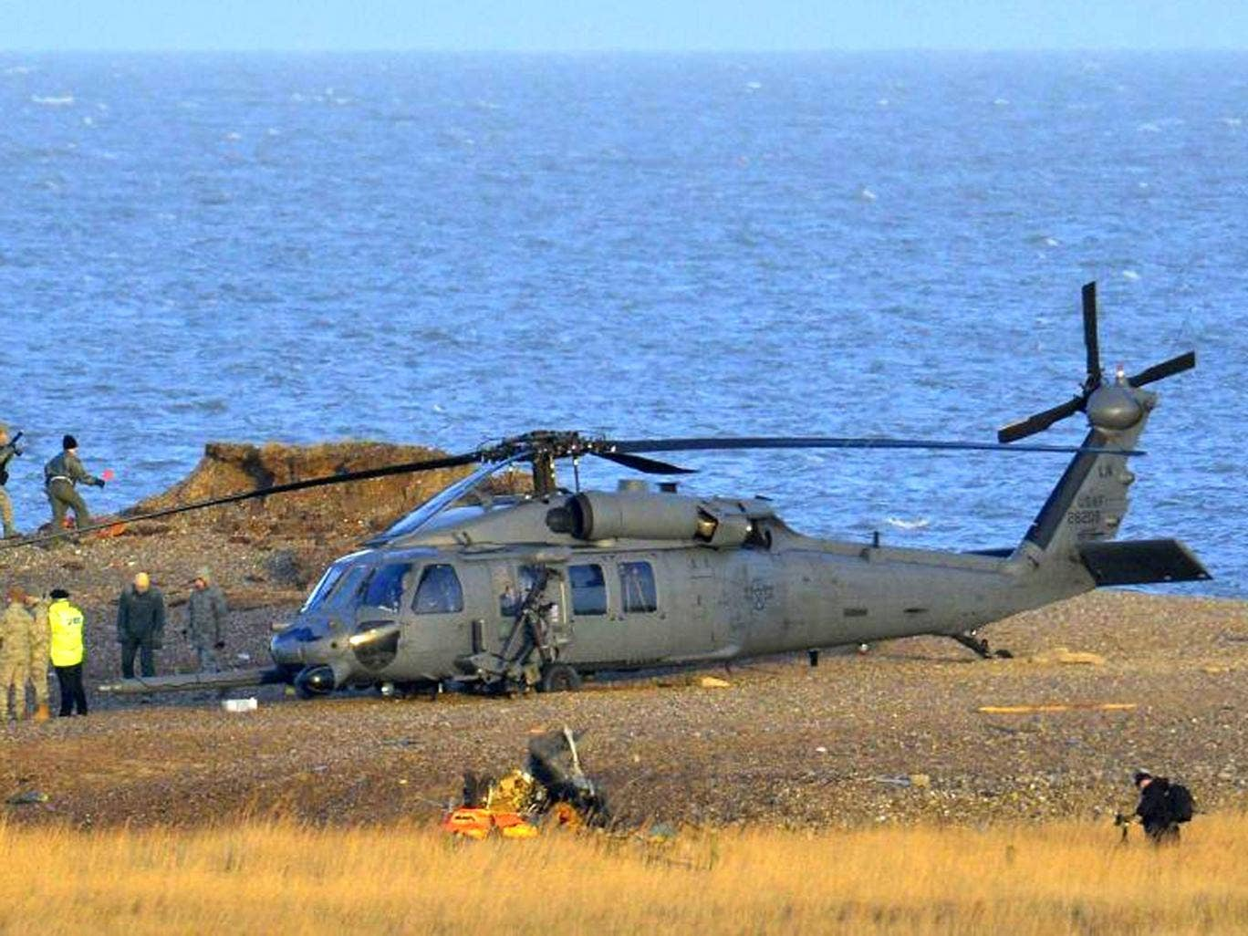 A Pave Hawk helicopter, military personnel and emergency services attend the scene of the crash on the coast near Cley