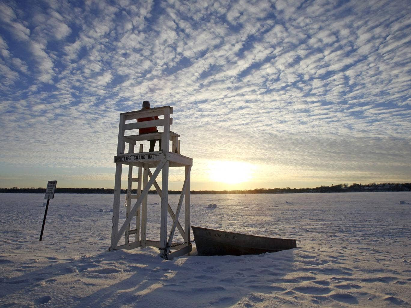 Lifeguard Jennifer Berry watches the sunset over a frozen Lake Calhoun in Minnesota during the cold snap