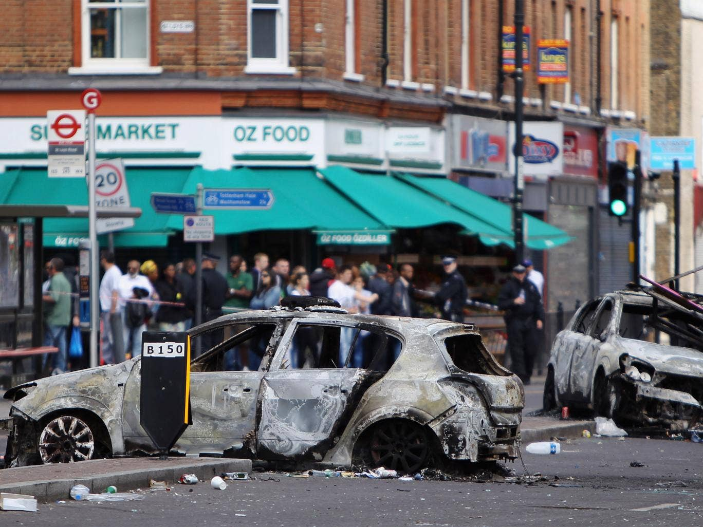 Burnt out cars lie in the road after riots on Tottenham High Road on August 7, 2011