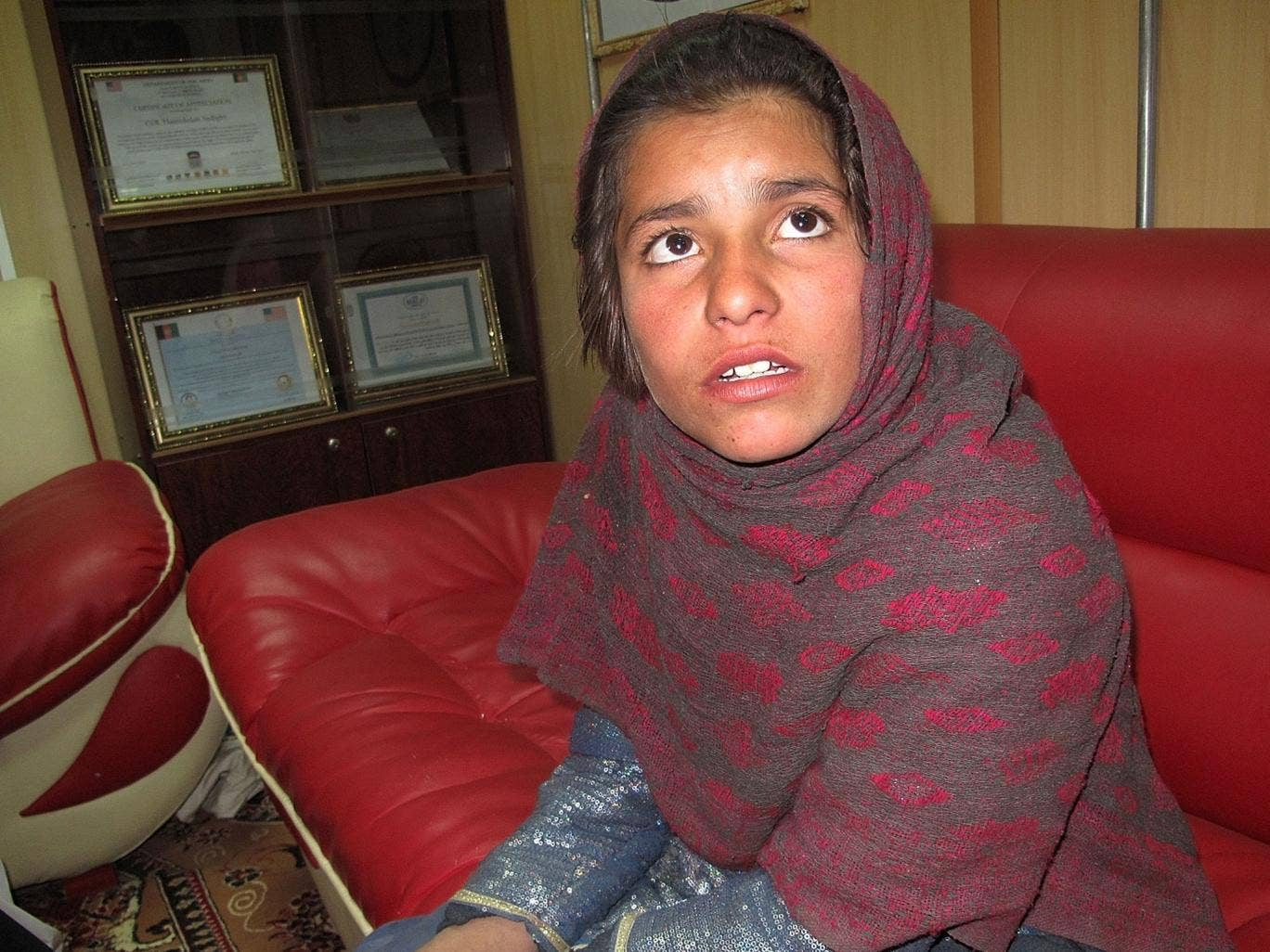Spozhmai, 10, who was about to be used by the Taliban as a suicide bomber, talks as she sits at a police office in Helmand province on January 6, 2014. Afghan authorities said on January 6 that they had detained a 10-year-old girl for attempting to carry