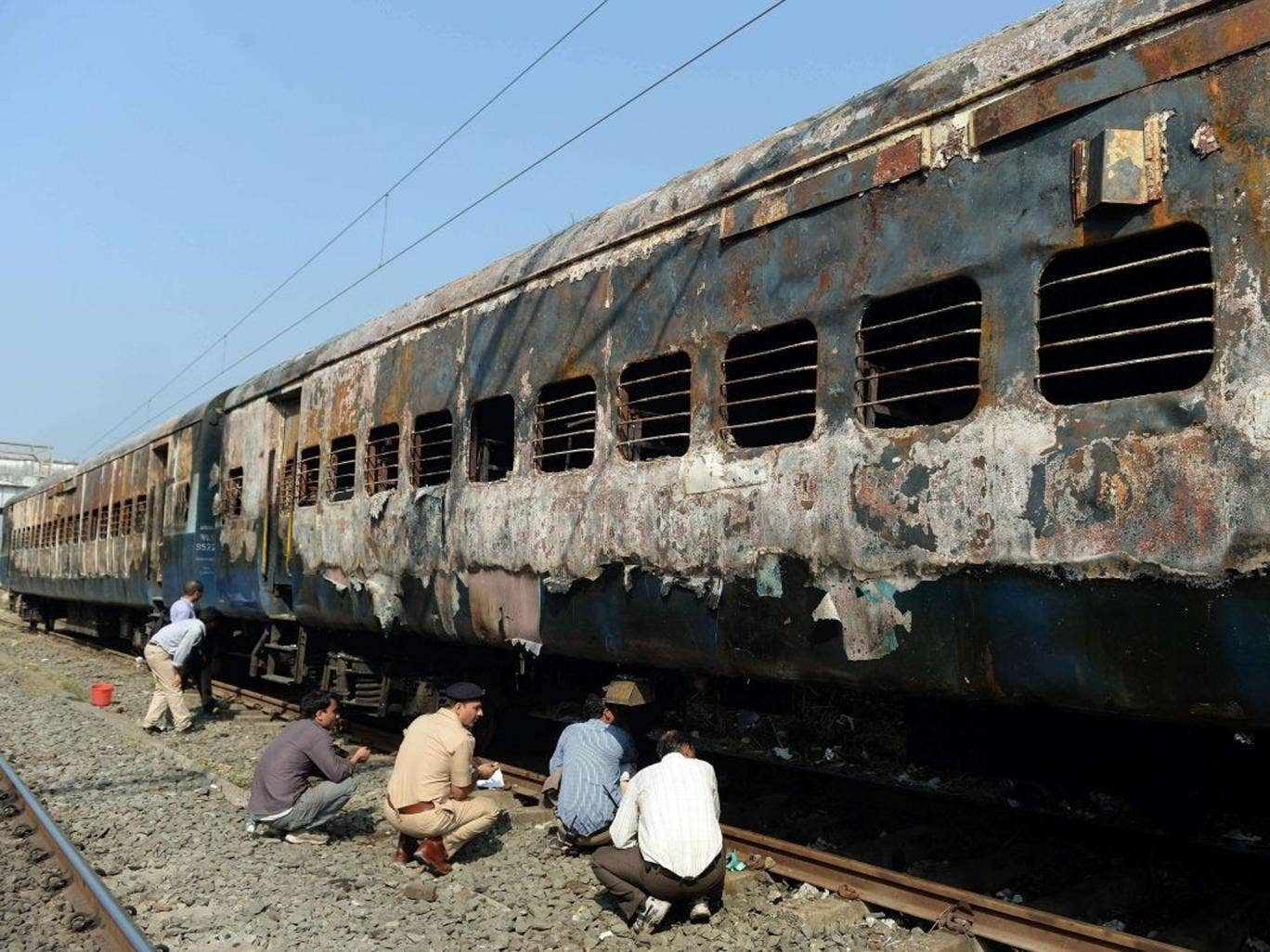 Indian railway and police officials inspect the burnt carriages of the long distance passenger train near Dahanu railway station