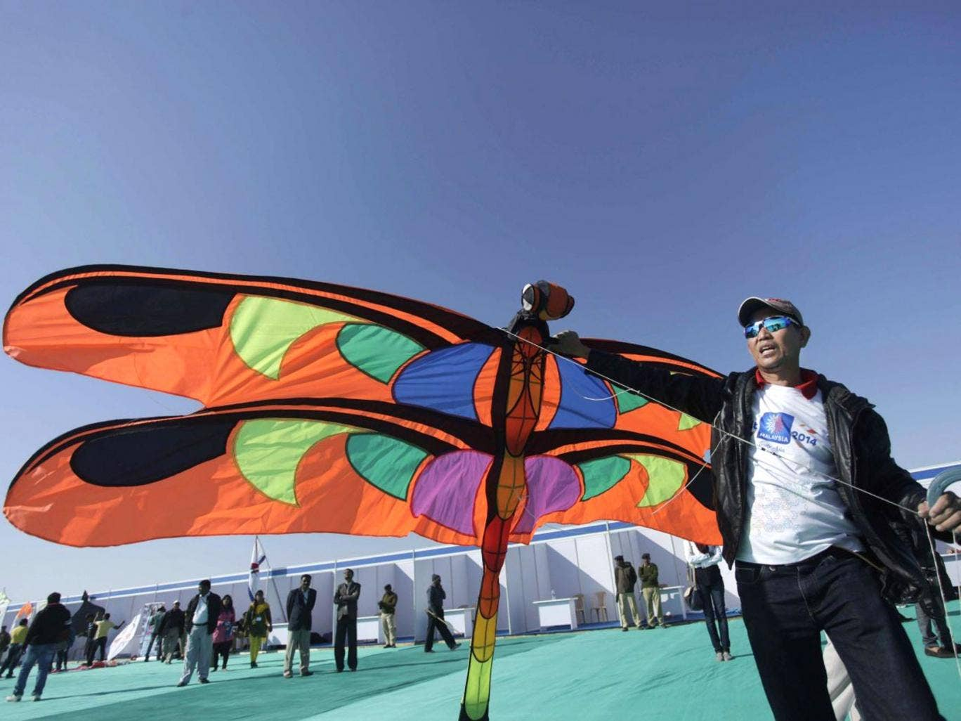 A man from Malaysia prepares to fly a kite during the International Kite Festival at white sand in the Rann of Kutch, a seasonal salt marsh located in the Thar Desert, in Dhordo, about 500 kilometers (311 miles) from Ahmadabad