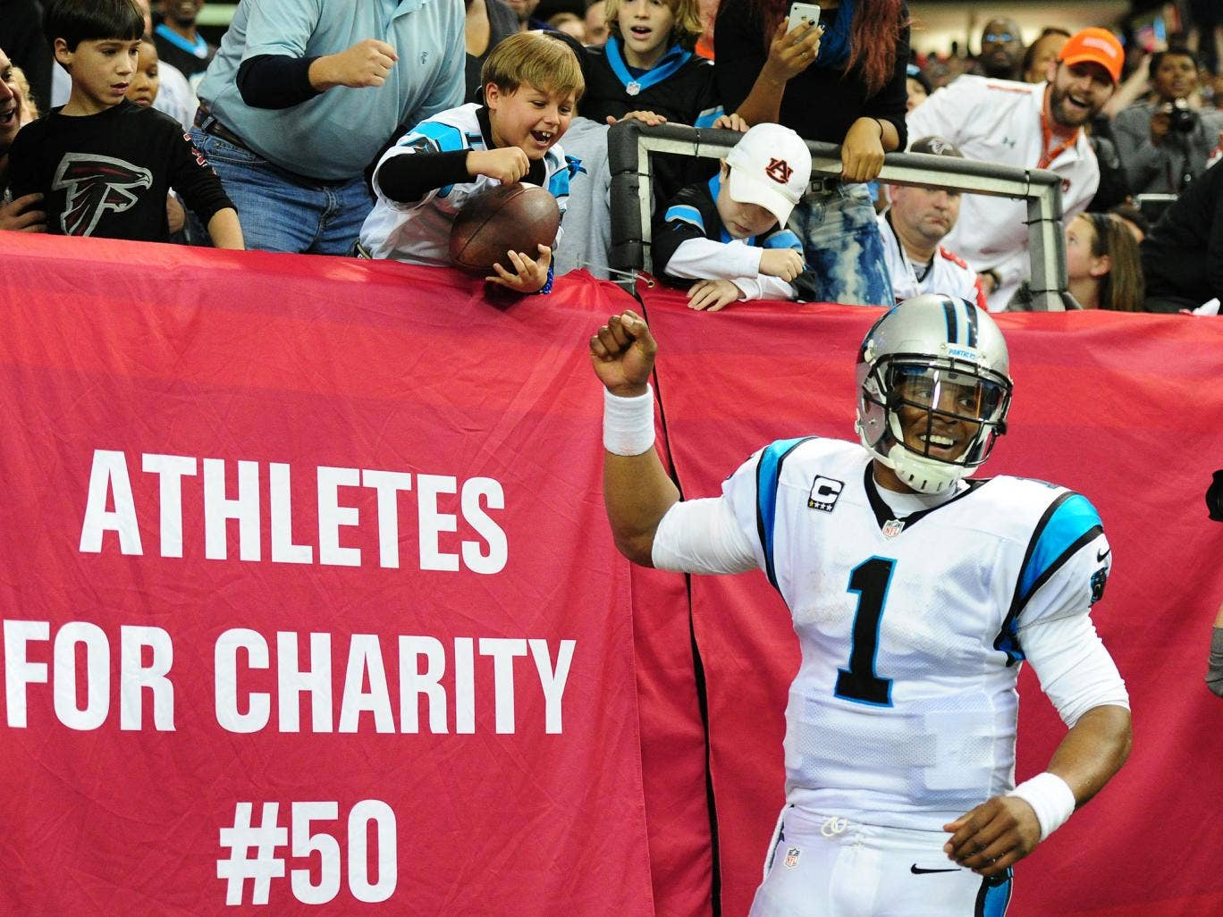 Carolina Panthers quarterback Cam Newton gives the ball to a young fan after running in a touchdown