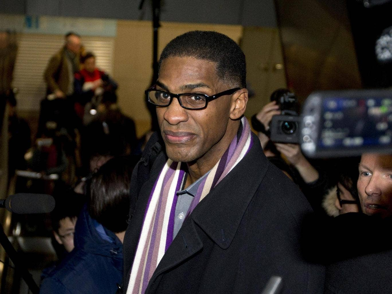 Former NBA basketball star Charles D. Smith is mobbed by journalists on an escalator upon arrival at the Beijing Capital International Airport in Beijing from Pyongyang, North Korea