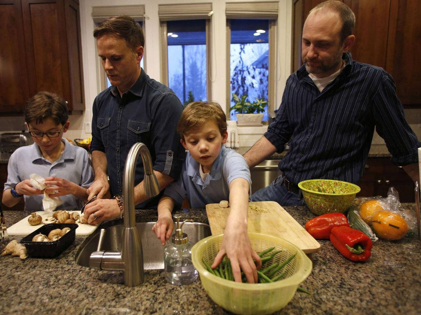Paul Redd-Butterfield, 2nd left, and his husband Tony Butterfield cook dinner with their adopted 11 year-old twin sons Lucas, left, and Liam at their home in Sandy, Utah. Paul and Tony were legally married on December 23, 2013. The US Government said it w