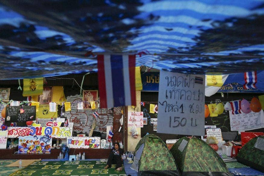 A man rests in the anti-government protesters' encampment near the Democracy monument in Bangkok