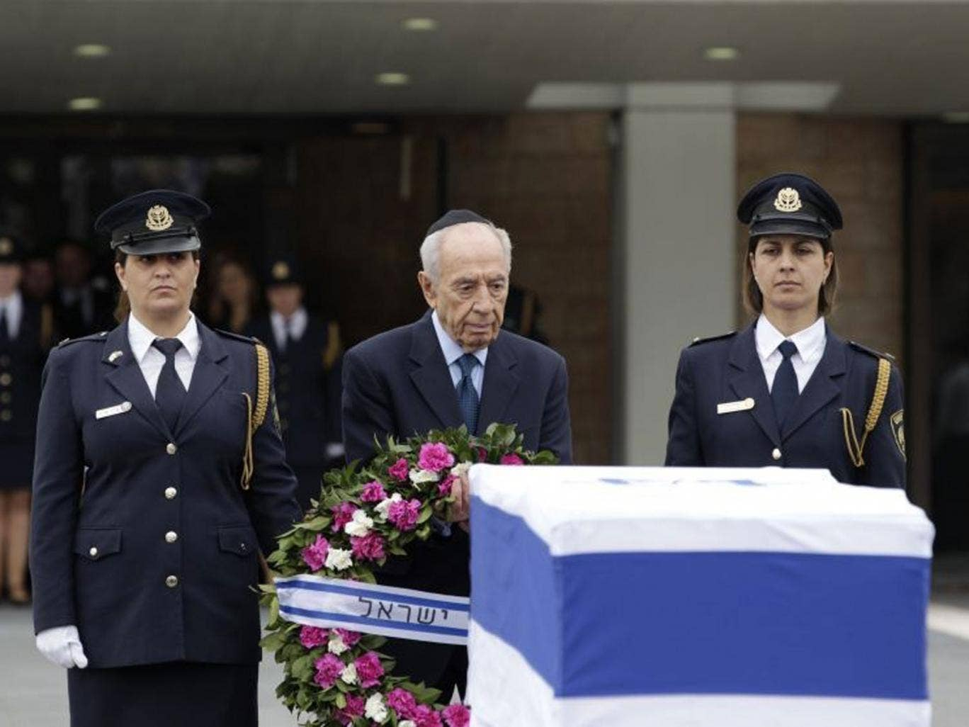 Israel's president Shimon Peres prepares to lay a wreath on the coffin of former prime minister Ariel Sharon
