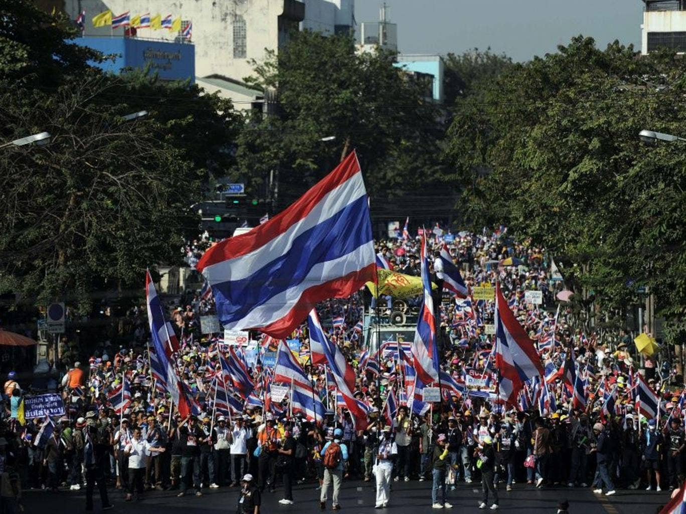 Thai anti-government protesters wave national flags as they march through the streets of Bangkok in a move to 'shut down' the city on 13 January 2014