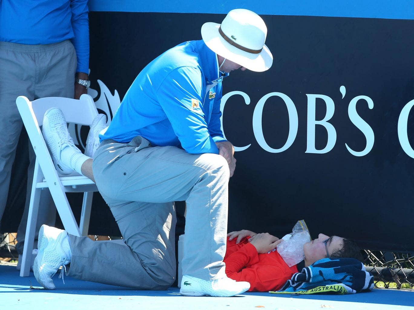 A ballboy faints in the heat, as Melbourne heads towards 43 degrees celsius during day two of the 2014 Australian Open at Melbourne Park
