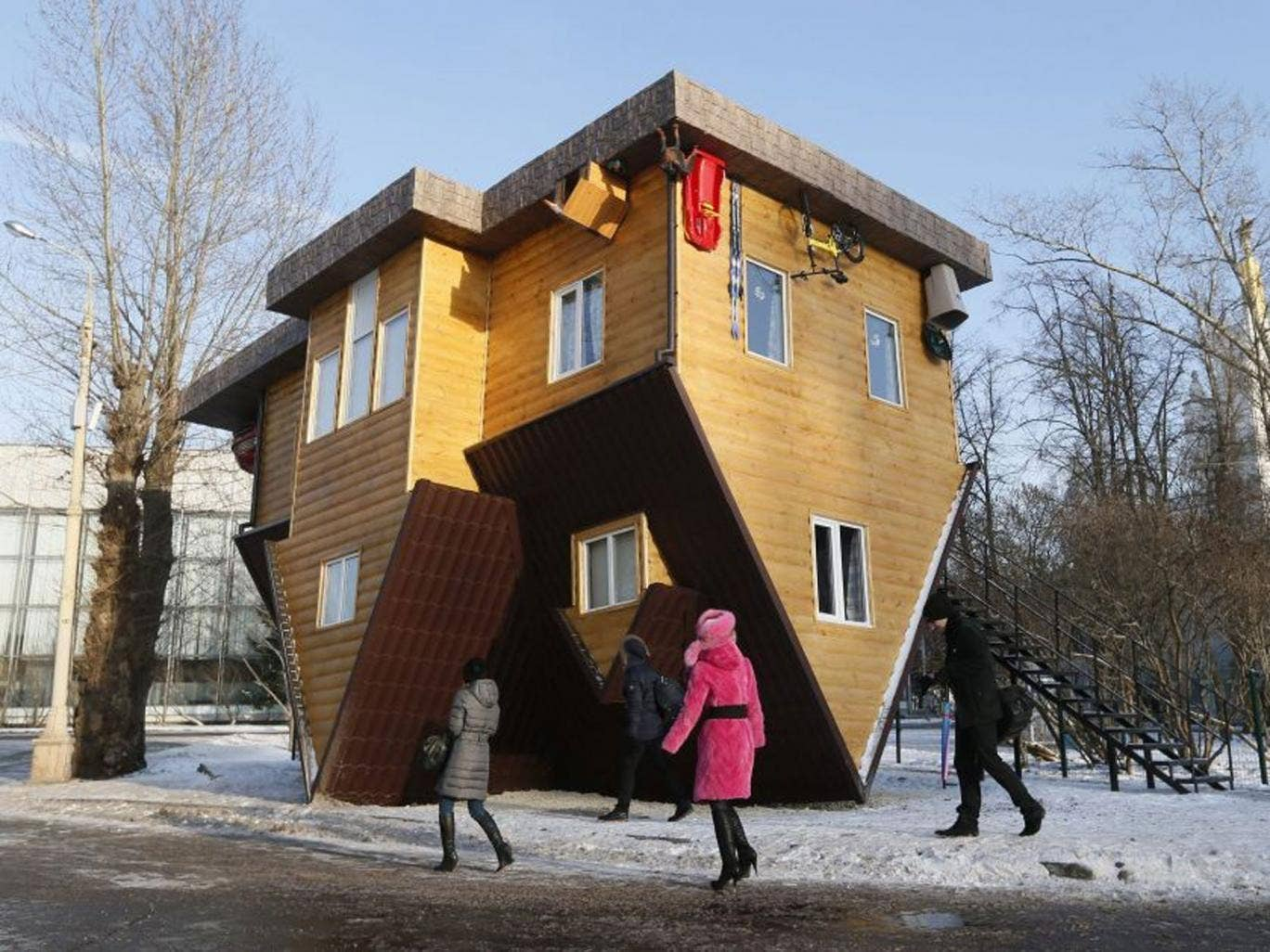 People look at an 'Upside Down House' attraction displayed at the VVTs the All-Russia Exhibition Center in Moscow