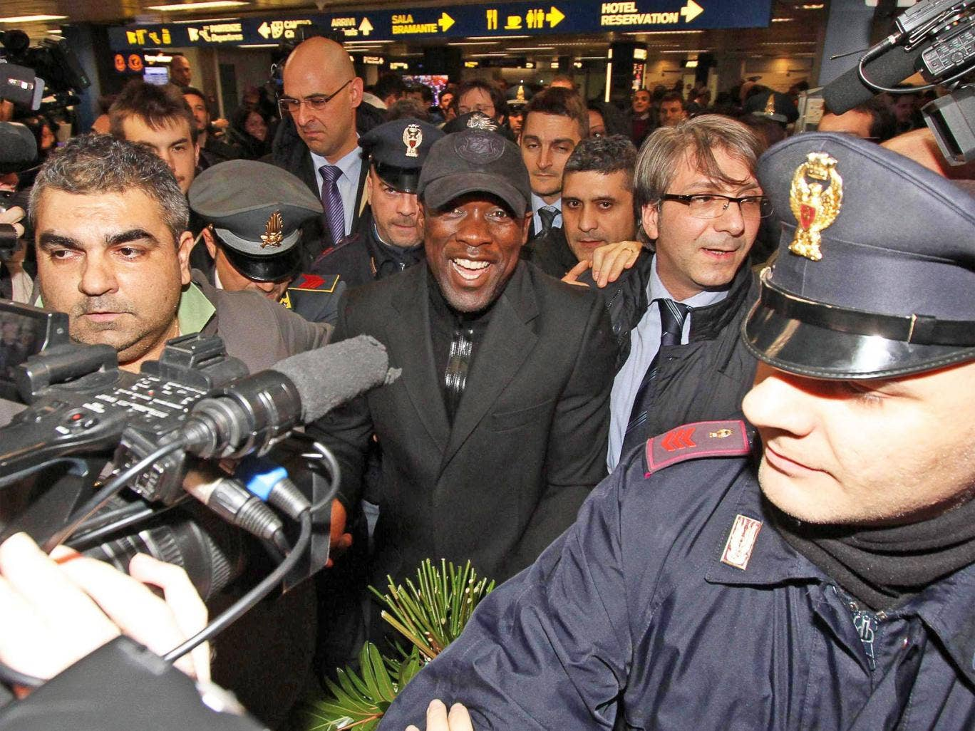 Clarence Seedorf (centre) is mobbed as he arrives at Linate Airport in Milan
