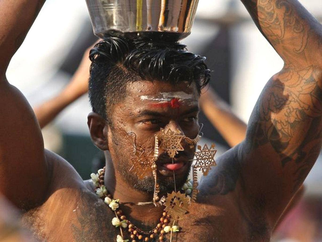 A Hindu devotee with needles protruding his cheeks walks towards the 272 steps taking up to the Batu Caves Temple during the Thaipusam Festival in Kuala Lumpur