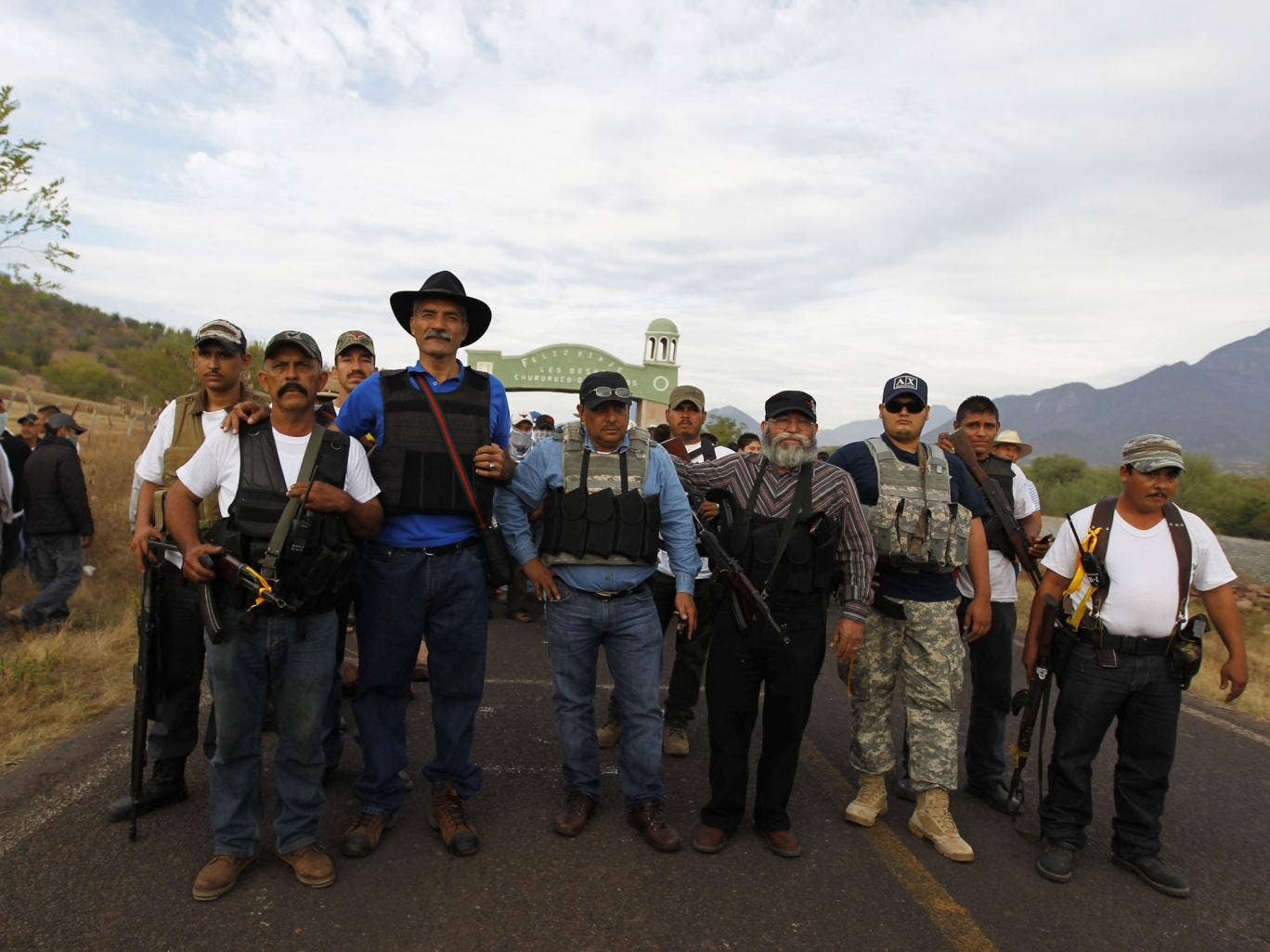 Dr Jose Manuel Mireles (third left), one of the leaders of the Michoacan vigilante group pictured with him. He has since been injured in an aircrash that could have been an attempt on his life