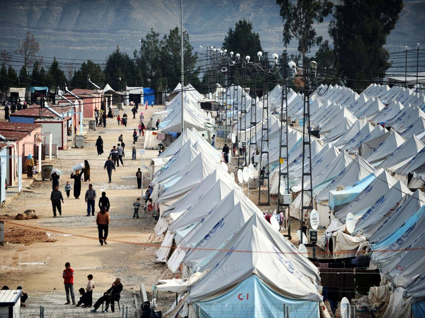 Syrian refugees walk among tents at Karkamis' refugee camp near the town of Gaziantep, south of Turkey