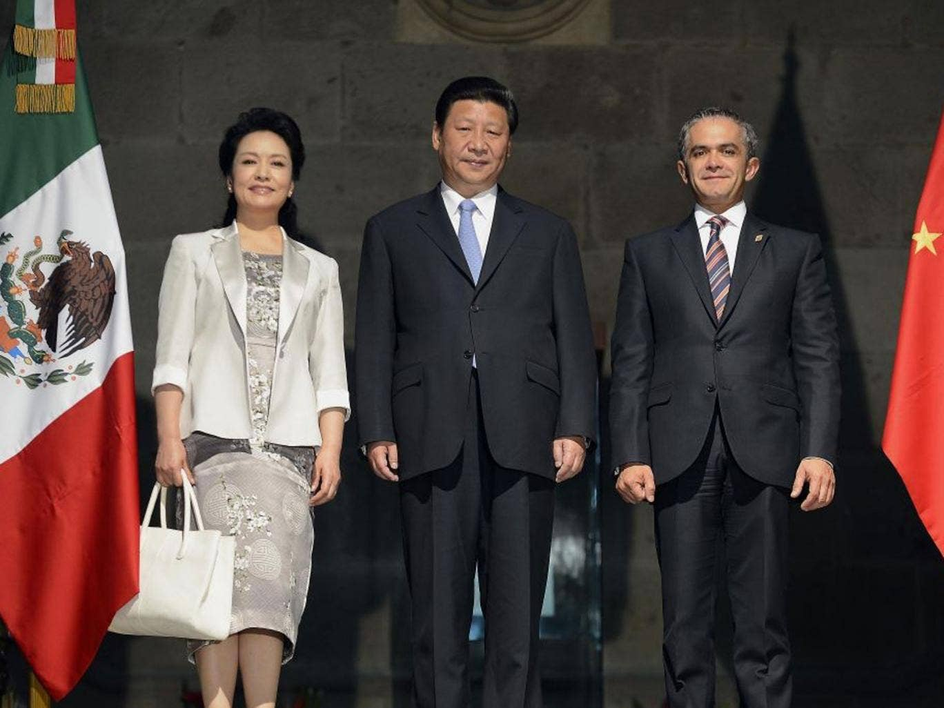 New direction: President Xi Jinping (pictured here with his wife and Mexico City's Mayor Miguel Mancera) is moving China away from state control of the investment process