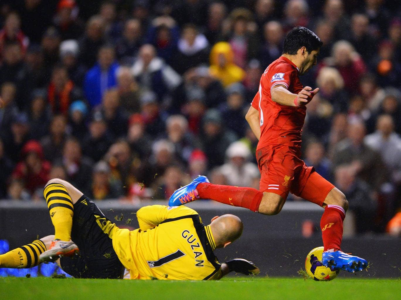 Luis Suarez goes down after Aston Villa goalkeeper Brad Guzan comes charging out of his goal, with referee Jon Moss giving the penalty